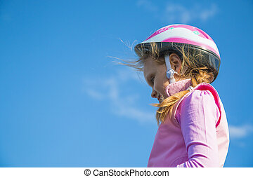 Girl in pink bicycle helmet against the blue sky with clouds. Close-up