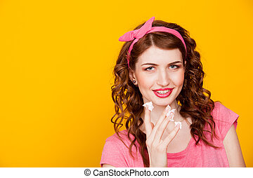 girl in pink dress pinup-style eats cake with cream