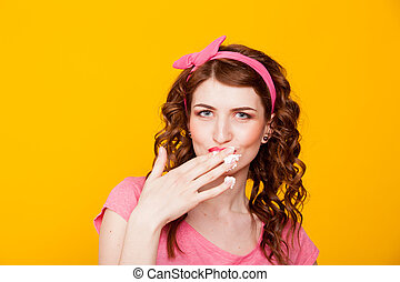 girl in pink dress pinup-style eats cream licks fingers
