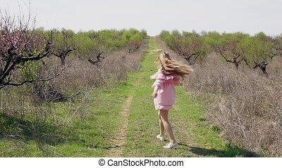 girl in pink dress runs on the road with grass