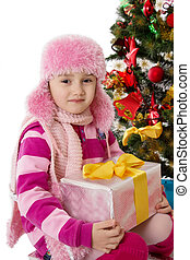 Girl in pink fur hat holding present under Chritmas tree