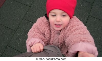 Adorable little girl wearing fluffy pink jacket and red warm hat unbuttons daddy clothes on city street close view from above