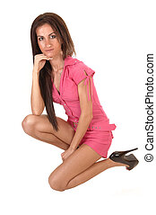 A beautiful young woman in a pink jumpsuit kneeling in the studio and her long hair falling over her shoulder, for white background.
