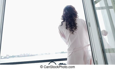 girl in pink light silk robe goes to the balcony to the...