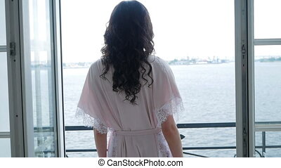 girl in pink light silk robe goes to the balcony to the window