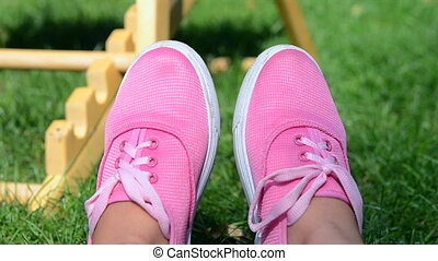 Girl in pink moccasins resting on green grass in summer