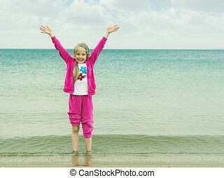 Girl in pink suit enjoys standing in sea water.