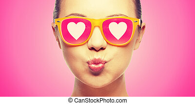 girl in pink sunglasses blowing kiss