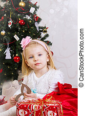 Girl in pink under Christmas tree