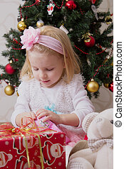 Girl in pink under Christmas tree holding giftbox