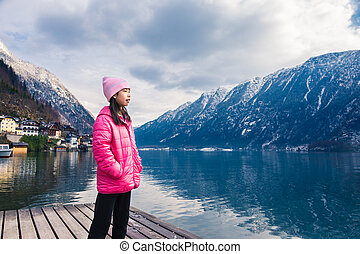 girl in pink winter cloth staning by a lake with blurred town and mountain range across the water in background