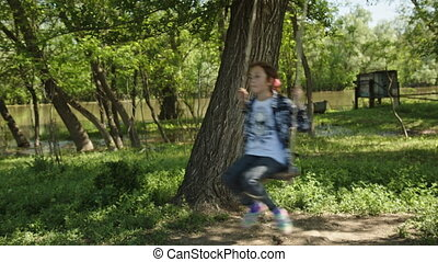 Girl in plaid shirt rides a rope swing - 8 years old girl in...