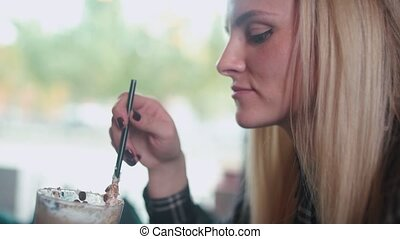 Girl in profile drinks coffee with whipped cream from a tall glass