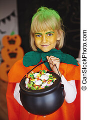 Girl in pumpkin costume holding a bowl full of candies