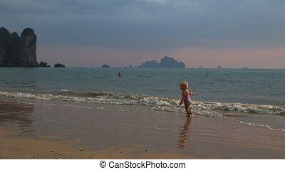 girl in purple swimsuit play in sea