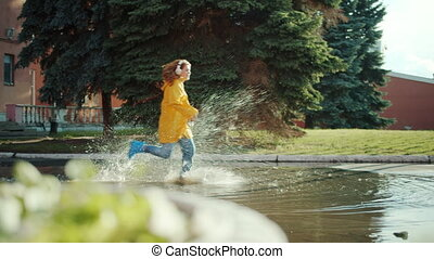 Girl in bright raincoat and gumboots is running in puddles wearing headphones having fun splashing in water. Lifestyle, leisure and devices concept.