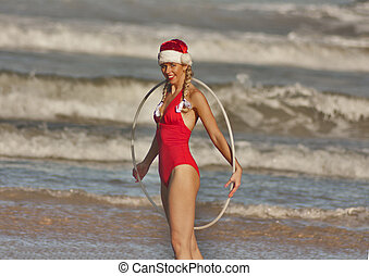 Girl in red and Christmas hat with hula hoop on the beach