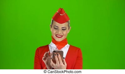 Girl in red attire looking at the phone is flipping through the pictures. Green Screen
