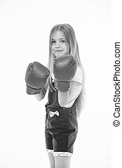 Girl in red boxing gloves, training strong spirit. Kid in pink jump suit isolated on white background. Child with serious face ready to fight. Self defense lesson, little boxer before combat