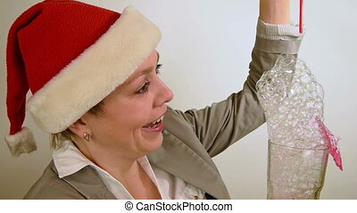 Girl in red Christmas Santa hat blows bubbles fun
