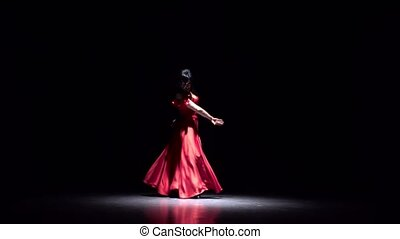 Girl in red dances flamenco. Black background. Silhouette. -...