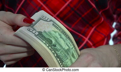 girl in red dress counts a pack of money in hands in slow motion