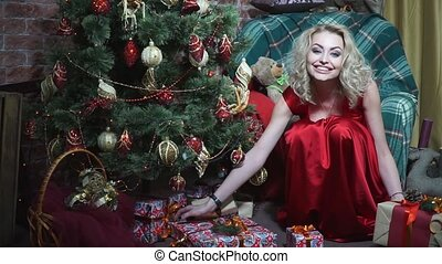 Girl in red dress has fun stacking presents under the Christmas tree