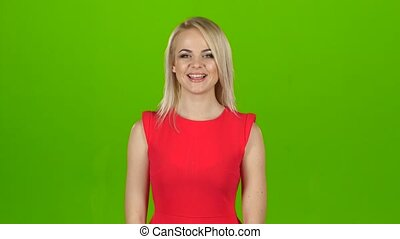 Girl in red dress is dancing for joy, green screen