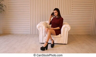 Girl in red dress sitting on a white leather couch.Full hd video