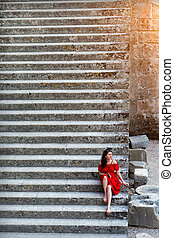 girl in red dress sitting on the steps