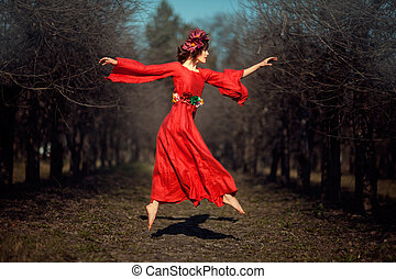 In autumn park floating girl in a red dress with a wreath on his head like a fairy tale.