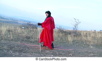 Girl in red dress walking on dry ground in skiing. Slow...