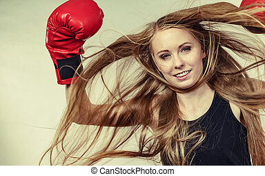 Girl in red gloves playing sports boxing
