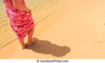 Girl in Red Long Dress Walks Barefoot along Water on Sand Beach