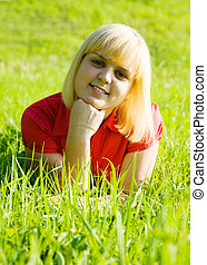 girl in red lying on  grass