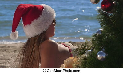 Girl in red Santa hat enjoying Christmas vacation time on tropical beach resort close-up