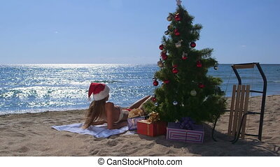 Girl in red Santa hat enjoying Christmas vacation time on tropical beach resort