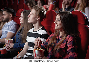 Girl in red shirt watching interesting film at cinema.