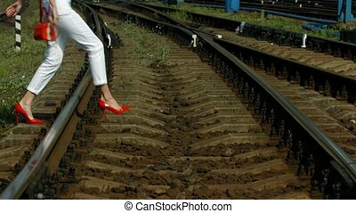 Railway transition. - Girl in red shoes hurry to the train....