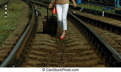 Girl traveling. - Girl in red shoes walking on the rails....