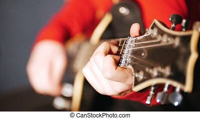 Girl in red sweater plays electric guitar