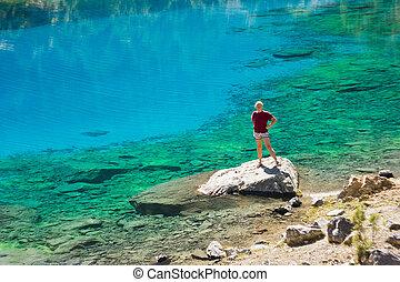 girl in red t-short near deep blue lake