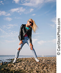 Girl in ripped jeans having fun on the shore of the blue sea...
