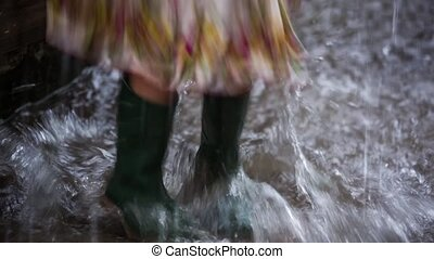 girl in rubber boots jumping over a puddle - legs of a girl...