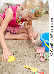 girl in sand playing