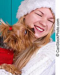 girl in santa cap with yorkie dog in red sweater