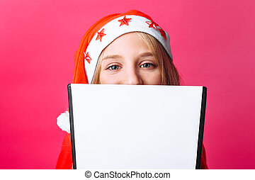 girl in Santa hat and tinsel on the neck, a teenager holding a tablet with a blank sheet, making plans for the New year on a red background