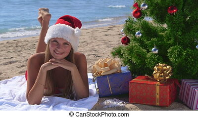 Girl in Santa hat celebrating Christmas on tropical beach