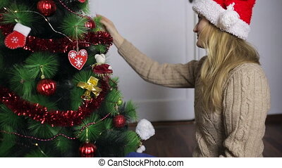 Girl in Santa hat decorates a Christmas tree