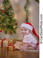 Girl in Santa hat dreaming under Christmas tree